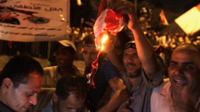 Supporters of deposed Egyptian president Mohamed Mursi burn an American flag during a rally on a main street in Cairo, July 19, 2013 (Reuters / Asmaa Waguih)