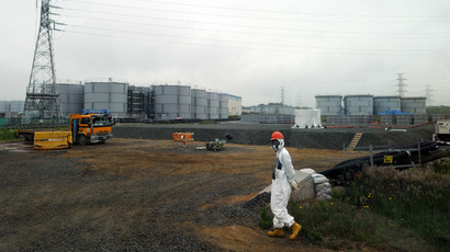 A construction worker walks near water tanks at Japan's Fukushima Dai-ichi nuclear plant in Okuma town in Fukushima prefecture on June 12, 2013. (AFP Photo)