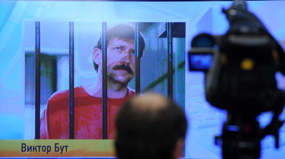 A journalist stands near a screen displaying convicted Russian arms smuggler Viktor Bout in Moscow, on April 12, 2012, during a teleconference with Bout from his US prison. (AFP Photo/Kirill Kudryavtsev)