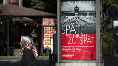 "A woman walks past a placard featuring a black-and-white photograph of the Auschwitz-Birkenau death camp and the tagline: ""Late but not too late"" as a campaign of Nazi-hunting Simon Wiesenthal Center seeking information on the last perpetrators of the Holocaust still at large nearly 70 years on, is pictured on July 23, 2013 in Berlin. (AFP Photo/Johannes Eisele)"