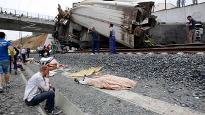 A wounded victim sits next to a body covered with a blanket after a train crashed near Santiago de Compostela, northwestern Spain, July 24, 2013 (Reuters / La Voz de Galicia)