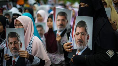 Malaysian Islamist hold posters of ousted Egyptian President Mohamed Morsi during a rally to oppose the military overthrow of the Islamist leader and subsequent killings in Egypt, outside the Egyptian embassy in Kuala Lumpur on July 26 2013 (AFP Photo)