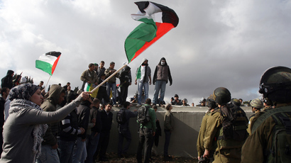 Palestinian demonstrators wave their national flag a protest against the construction of Israel's separation barrier in the West Bank village of Qalandia, near Ramallah (AFP Photo / Abbas Momani)