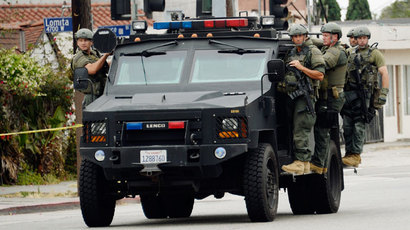 Los Angeles County Sheriff's SWAT team members standing on a armored car arrive to help Los Angeles Police Department officers during a massive manhunt for a suspect who attempted to kill two detectives on June 25, 2013 in Los Angeles, California.(AFP Photo / Kevork Djansezian)