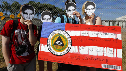 "Protesters wearing masks of U.S. whistleblower Edward Snowden hold a sign disparaging the National Security Agency (NSA) outside the ""Dagger Complex"", which is used by the U.S. Army intelligence services, during a demonstration against the NSA and in support of Snowden in Griesheim, 20km (12.4 miles) south of Frankfurt, July 20, 2013. (Reuters/Kai Pfaffenbach)"