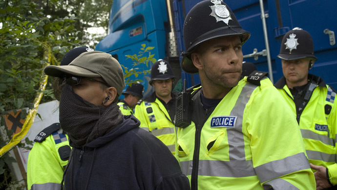 A demonstrator is detained by police as they escort a lorry containing drilling equipment to a drilling site outside the village of Balcombe in southern England July 27, 2013. (Reuters/Kieran Doherty)