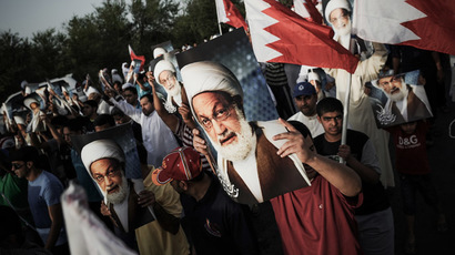 Bahraini demonstrators hold pictures of Bahraini senior Shiite cleric Sheikh Issa Qassem during a protest against the regime and to show solidarity with the cleric in the village of Abu Saiba, west of Manama, on May 17, 2013. (AFP Photo)