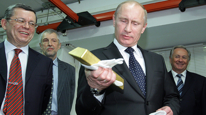 Vladimir Putin holds a gold bar while visiting the Central Depository of the Bank of Russia (AFP Photo / Alexsey Druginyn)