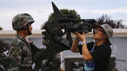 A journalist takes a close-up picture of a soldier from Air Defence Brigade, 47th Combined Corps, PLA during a display organized for media by Chinese government in Lintong, Shaanxi province July 29, 2013. (Reuters / Petar Kujundzic)