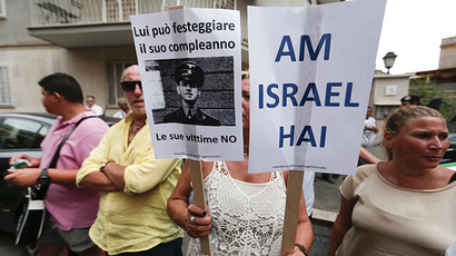 "A woman holds signs reading, ""The Jewish People Live"" (R) and ""He can celebrate his birthday, his victims no"" during a protest against convicted former Nazi SS captain Erich Priebke in Rome July 29, 2013. (Reuters)"
