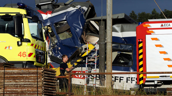 A rescue worker stands near two Swiss regional trains after a head-on collision near Granges-Pres-Marnand near Payerne in western Switzerland July 29, 2013.(Reuters / Denis Balibouse)