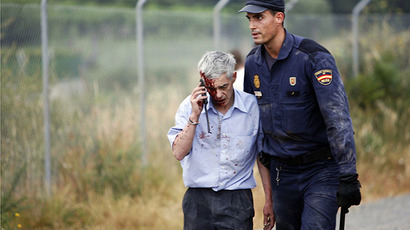 An injured man, identified by Spanish newspapers El Pais and El Mundo as the train driver Francisco Jose Garzon, is helped by a policeman after a train crashed near Santiago de Compostela, northwestern Spain, July 24, 2013. (Reuters / Oscar Corral)