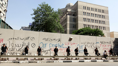 Security personnel stand guard near a wall with graffiti at the U.S. embassy in Cairo (Reuters)