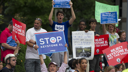 Protesters hold signs against the building of the Keystone XL Pipeline (AFP Photo / Saul Loeb)