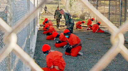 Detainees in orange jumpsuits sit in a holding area under the watchful eyes of military police at Camp X-Ray inside Naval Base Guantanamo Bay, Cuba, during their processing into the temporary detention facility (Reuters/U.S. Department of Defense/Petty Officer 1st class Shane T. McCoy)