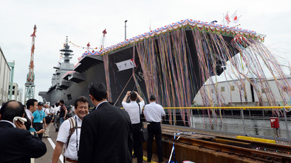 Journalists look at Japan's new warship, the DDH183 Izumo, during the launch ceremony at the port in Yokohama on August 6, 2013