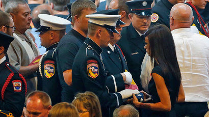 An honor guard presents Juliann Ashcraft (R), wife of fallen Granite Mountain Hotshots firefighter Andrew Ashcraft, with an American flag during a memorial service at Tim's Toyota Center in Prescott Valley, Arizona July 9, 2013.(Reuters / David Kadlubowski)
