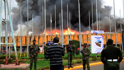 General Service (GSU) officer stand outside the burning Jomo Kenyatta international airport on August 7, 2013 (AFP Photo / Stringer)