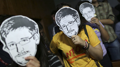 People use masks with pictures of former NSA contractor Edward Snowden (Reuters / Ueslei Marcelino)