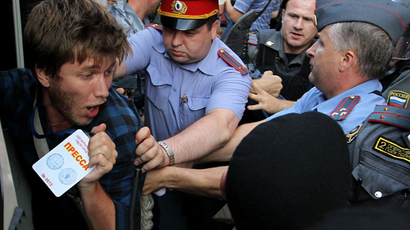 A young man shows his press ID as Russian police detain him during a protest action in Moscow (AFP Photo / Aleksei Sazonov)