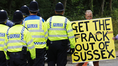 A demonstrator stands in the road as police escort a lorry to a site run by Cuadrilla Resources, outside the village of Balcombe in southern England August 6, 2013. (Reuters / Luke MacGregor)