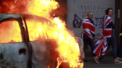 People draped with the Union flags walk past a burning car after loyalist protesters attacked the police with bricks and bottles as they waited for a republican parade to make its way through Belfast City Centre August 9, 2013. (Reuters/Cathal McNaughton)