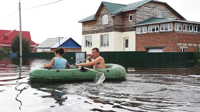 Local people in a boat in the flood village of Vladimirovka in Amur Region. (RIA Novosti/Belozerov Ivan)
