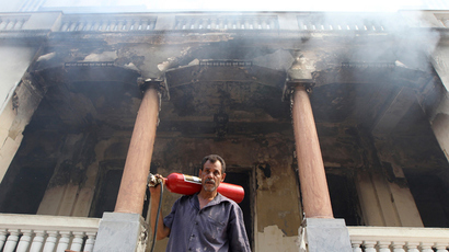 A man walks from a government building that was set ablaze in Giza's district of Cairo, August 15, 2013 (Reuters / Muhammad Hamed)