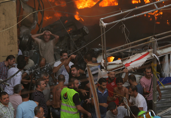 People react as the they gather around the site of an explosion in Beirut's southern suburbs, August 15, 2013 (Reuters / Mahmoud Kheir)
