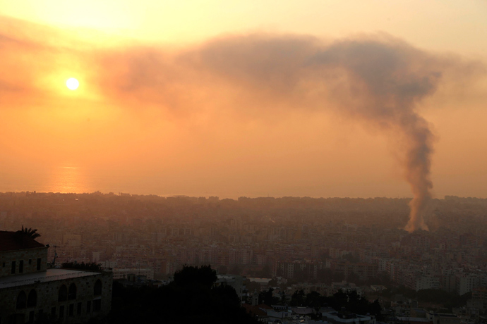 Smoke rises behind buildings from the site of an explosion in Beirut's southern suburbs, August 15, 2013 (Reuters / Mohamed Azakir)