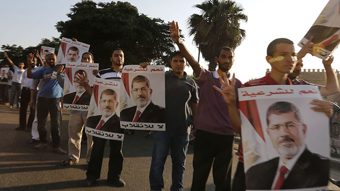 Supporters of deposed Egyptian President Mohamed Mursi hold up posters of him during a protest along Zahara street in Cairo August 18, 2013. (Reuters / Louafi Larbi)