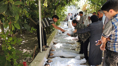 A handout image released by the Syrian opposition's Shaam News Network shows a man taking the body of a child wrapped in shrouds from a line of victims which Syrian rebels claim were killed in a toxic gas attack by pro-government forces in eastern Ghouta, on the outskirts of Damascus on August 21, 2013. (AFP Photo / Daya Al-Deen)