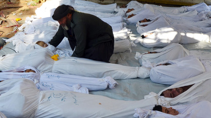A man holds the body of a dead child among bodies of people activists say were killed by nerve gas in the Ghouta region, in the Duma neighbourhood of Damascus August 21, 2013. (Reuters/Bassam Khabieh)