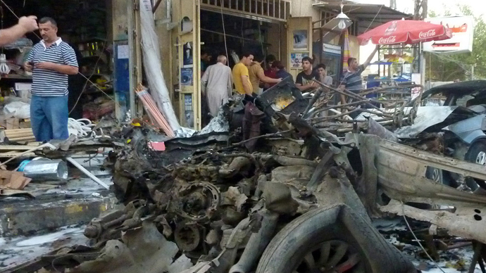 Iraqi men inspect the site of a car bomb attack on August 6, 2013 in Baghdad's Karrada commercial district (AFP Photo)