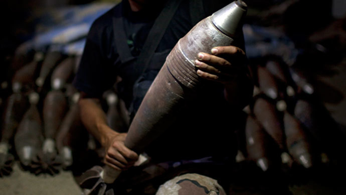 A rebel fighter holds an improvised mortar shell, one of many stacked at a factory in the city of Aleppo, Syria's commercial capital, on July 7, 2013.(AFP Photo / Jm Lopez)