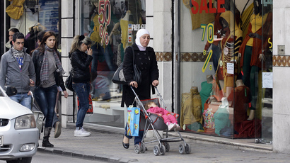 People walk past shop windows in the Syrian capital Damascus (AFP PHhoto / Louai Beshara)