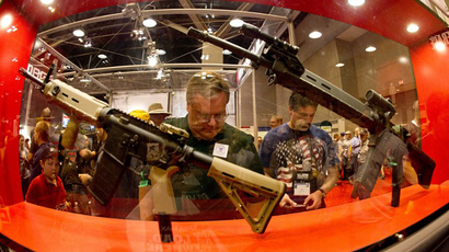 Gun enthusiasts look at various firearms on the floor at the National Rifle Association (NRA) Annual Meetings and Exhibits in St. Louis, Missouri. (AFP Photo / Karen Bleier)