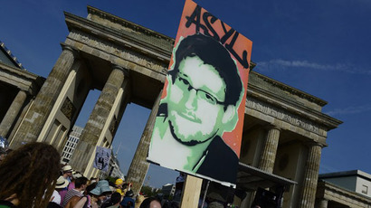 Demonstrators hold up a placard in support of former US agent of the National Security Agency, Edward Snowden in front of Berlin's landmark Brandenburg Gate as they take part in a protest against the US National Security Agency (AFP Photo / John Macdougall)