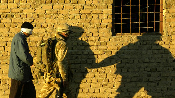 Iraqi suspect is led by a British soldier during a raid early 25 November 2004, in a village on the east bank of the Euphrates, south of Baghdad. (AFP Photo / Michael Dunlea)