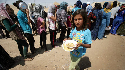 Syrian-Kurdish refugee families queue to get food at the Quru Gusik refugee camp, 20 kilometres east of Arbil, the capital of the autonomous Kurdish region of northern Iraq, on August 29, 2013.  (AFP Photo / Safin Hamed)