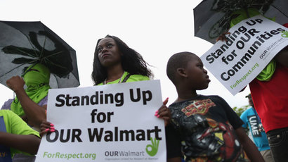 Sarabine Milien (L) and her nephew, Isiaha Chery, join with other protesters in front of a Walmart store as they target the company which they say needs to improve working conditions and rehire workers they say were fired for engaging in labor activities on September 5, 2013 in Miami Gardens, Florida.(AFP Photo / Joe Raedle)