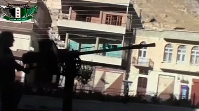 A Syrian rebel fires a heavy machine gun mounted on the back of a vehicle in Maaloula, a suburb of Damascus, in this image taken from a September 4, 2013 video footage obtained from a social media website (Social media website via Reuters TV)