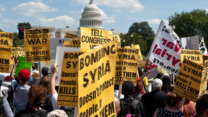 A Syrian girl (2nd L) and an Iranian girl hold signs outside the Rayburn House office building across from the US Capitol in Washington during a demonstration against US intervention in Syria on September 7, 2013. (AFP Photo/Nicholas Kamm)