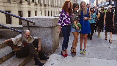 Fashionistas pose for photographs in front of a homeless man outside Moynihan Station following a showing of the Rag & Bone Spring/Summer 2013 collection during New York Fashion Week September 7, 2012. (Reuters/Lucas Jackson)