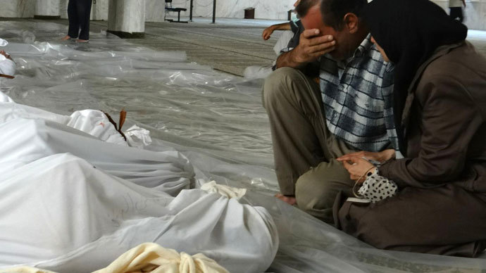 Syrian couple mourning in front of bodies wrapped in shrouds ahead of funerals following what Syrian rebels claim to be a toxic gas attack by pro-government forces in eastern Ghouta, on the outskirts of Damascus on August 21, 2013.(AFP Photo / Shaam News Network )