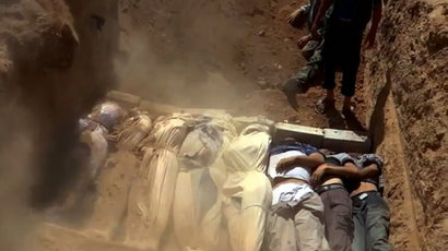 Syrians covering a mass grave containing bodies of victims that Syrian rebels claim were killed in a toxic gas attack by pro-government forces.(AFP Photo  / Local Committee Of Arbeen)