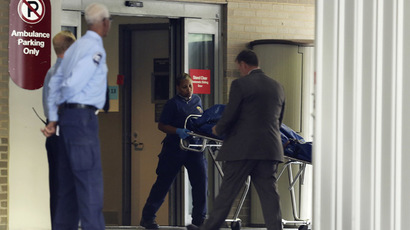 An official from the Washington, DC Office of the Medical Examiner wheels a body on a gurney out of the emergency room at George Washington University Hospital shortly after it was announced that the first victim of the shooting at the Navy Yard in Washington had died at the hospital, in Washington September 16, 2013.  (Reuters/Gary Cameron)