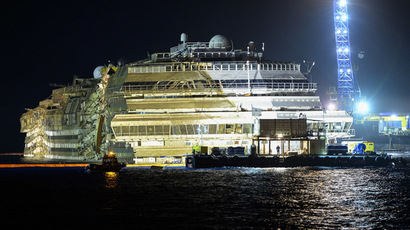 The wreck of Italy's Costa Concordia cruise ship begins to emerge from water on September 17, 2013 near the harbour of Giglio Porto. (AFP Photo/Andreas Solaro)