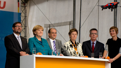 German Chancellor Angela Merkel (2nd,L) and Defence Minister Thomas de Maiziere (2nd,R) watch a quadcopter (drone) crashing onto the stage during an election campaign event of her German Christian Democratic Union (CDU) party in Dresden, eastern Germany on September 15, 2013 (AFP Photo / Odd Anderson)