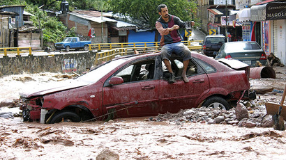 A man sits atop a car while trying to cross a flooded street in Chilpancingo, state of Guerrero, Mexico, on September 17, 2013. (AFP Photo / Eduardo Guerrero)